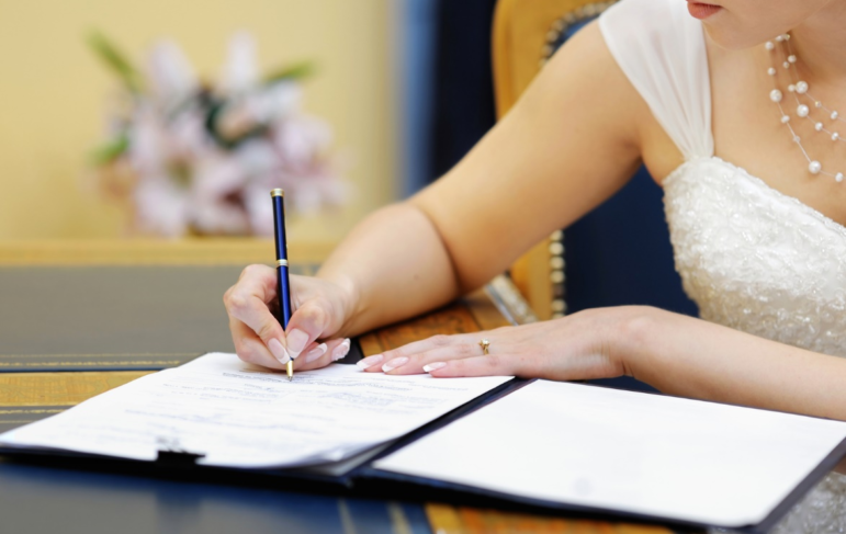 a bride signing marriage documents